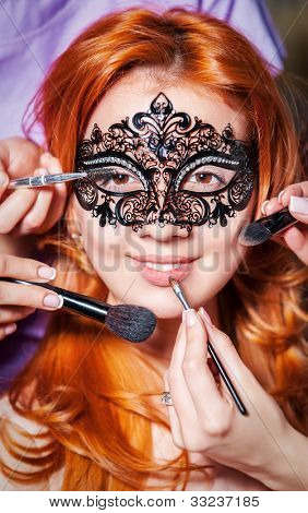 Portrait beautiful red long wavy, curly hair girl in mask with make-up brushes near face