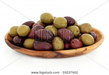 Green and black olives in an olive wood bowl over white background.