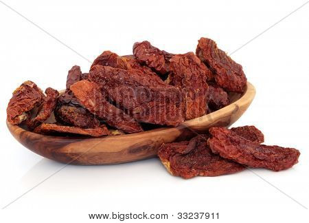 Sun dried salted tomatoes in a rustic olive wood bowl and scattered over white background.