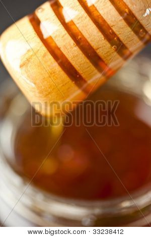 Honey dipper on top of a honey jar against a black background