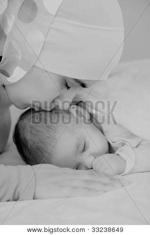 Hermoso bebé de dos meses de edad en las manos de las madres musulmanas.