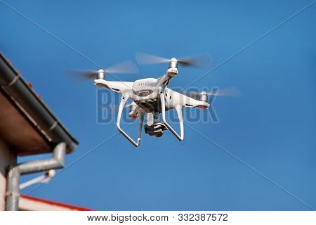 poster of Drone Quad Copter Fly On Blue Sky In Background. Modern Drone Is Flying In Air, To Take Photos And R