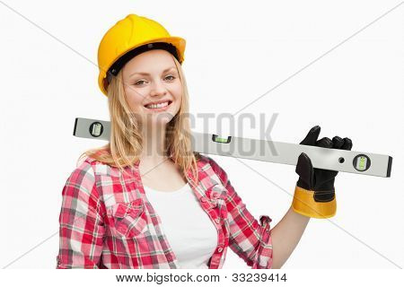 Smiling woman holding a spirit level against white background
