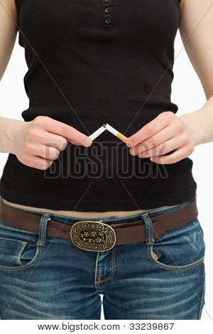Woman breaking a cigarette with her hands against white background