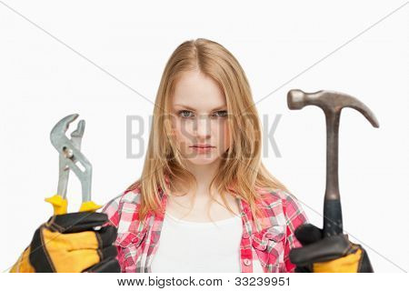 Serious woman holding a hammer and and a wrench against white background