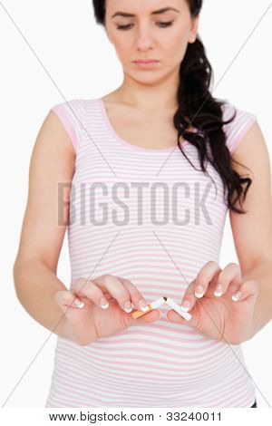 Pregnant woman breaking a cigarette against white background