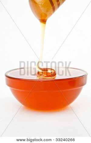 Honey trickle dropping in full honey bowl against a white background