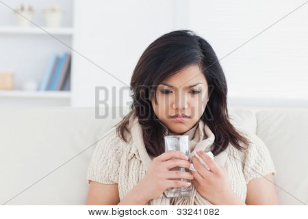 Woman holding a glass of water while being cold in a living room