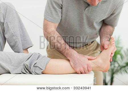 Doctor examining the foot of a woman while standing in a well-lit room
