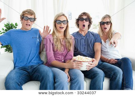 Shocked friends with some popcorn as they get scared by a scary movie