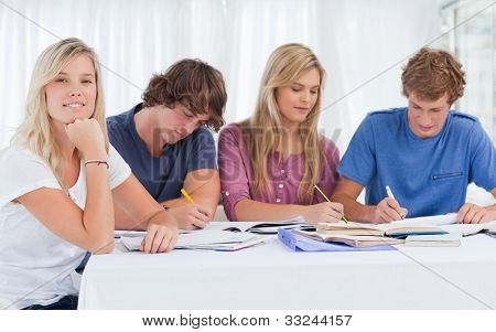 A study group working hard as one girl smiles and looks at the camera with her hand resting on her chin supporting her head