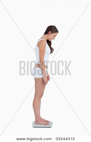 Smiling woman standing on weighing scales against a white background