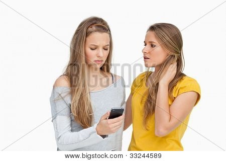 Upset young woman consoled by her friend against white background
