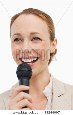 Enthusiastic woman in a suit speaking with a microphone against white background