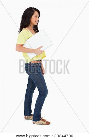 Side view of a beautiful Latin student holding a laptop against white background