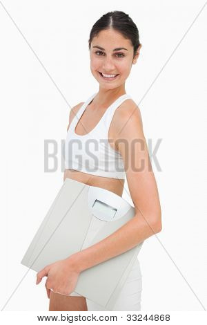 Portrait of a slim young woman holding a scales against white background