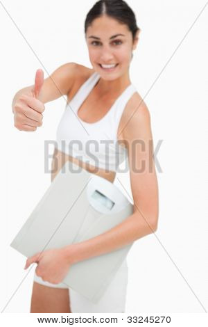 Slim young woman holding a scales the thumb-up against white background