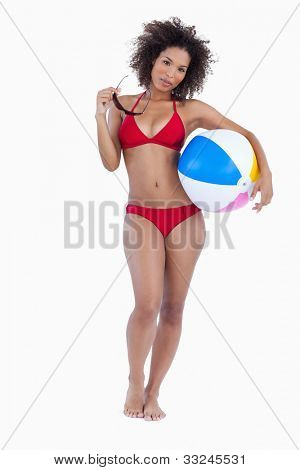 Brunette holding her sunglasses and a beach ball against a white background