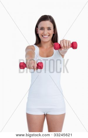 Red weights being held by a young brunette against a white background