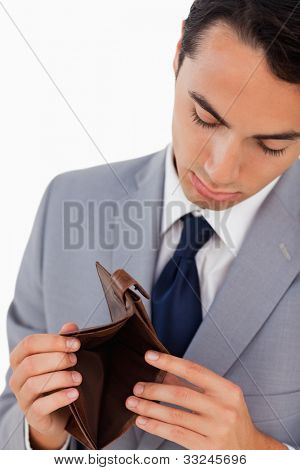 Man in a suit showing his empty wallet against white background