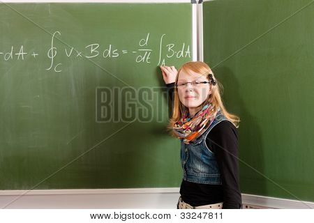 Education - Child or pupil at blackboard in school in math, the kid is very intelligent for it calculates difficult equations