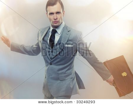 Businessman with a briefcase on abstract background