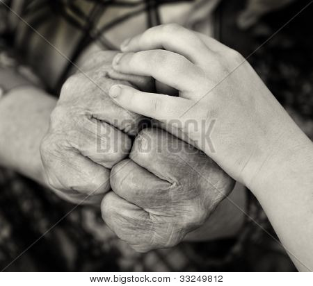 Hands of the old woman and child hand above