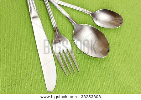 Fork, spoon and knife on a green tablecloth