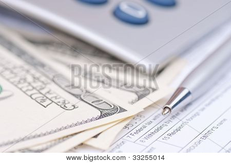 Macro shot of pen, hundred-dollar bills and cropped calculator