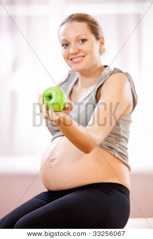 Young pregnant woman holding green apple