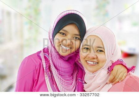 Happy Muslim women standing inside house