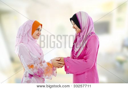 Muslim woman in traditional clothing greeting to each other, indoor.