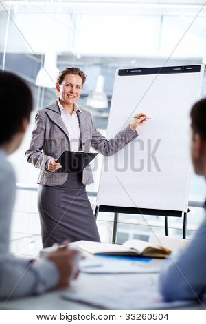 Smart businesswoman standing by whiteboard and explaining her ideas