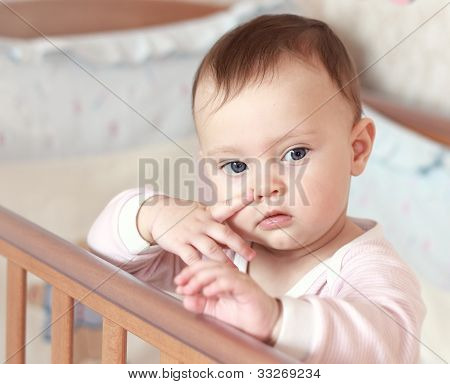 Funny Small Baby Girl Holding Finger On Face Standing In Bed