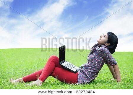 Mujer asiática con ordenador portátil al aire libre