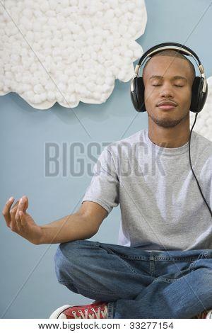 African Man meditieren und das Tragen von Kopfhörern