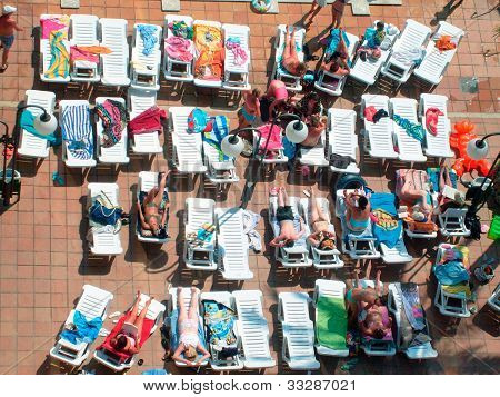 Overhead view of some sunbathers on sun terrace in tourist hotel.