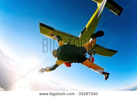 Tandem skydiver in action parachuting, seen in mid air position.