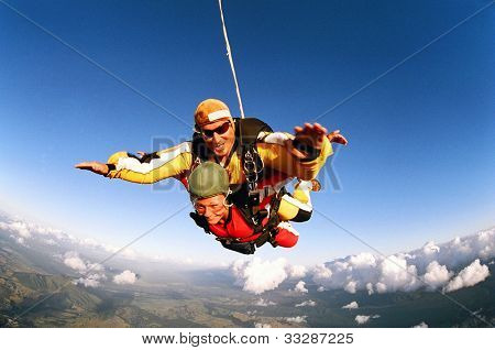 Tandem skydivers smiling in mid-air position over cloudscape and earth.