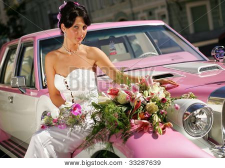 Pretty young adult bride sat on hood of pink wedding car limousine.