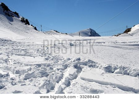 Closeup of ski tracks in snowy Alpine mountainous landscape.