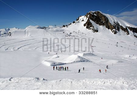 Scenic landscape of skiers in Alpine mountains with peak in background, Crans Montana, Switzerland,