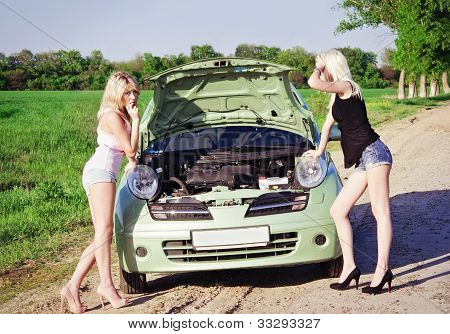Two Sexy Blonde Girls Stand By The Broken Car