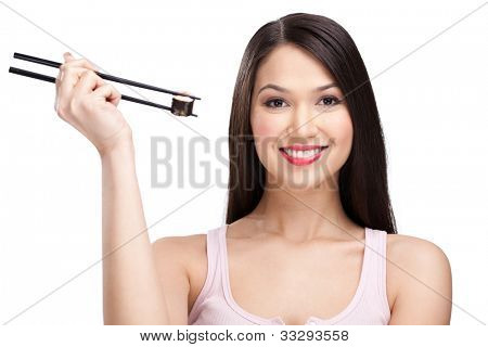 Young attractive woman holding sushi with a chopsticks, isolated on white