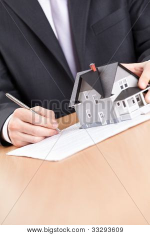 Conceito imóveis - contraem de sinais de homem de negócios por trás do modelo de arquitetura doméstico