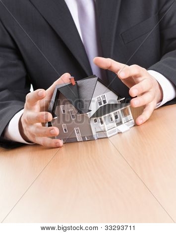 Real estate concept - business man hands around home architectural model