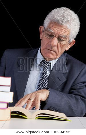 Senior businessman holding a page from an open book (isolated on black)