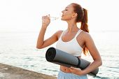 Image of redhead young woman in sportswear holding yoga mat and drinking water while doing workout b poster