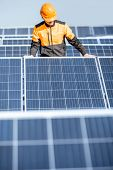 Well-equipped Worker In Protective Orange Clothing Installing Or Replacing Solar Panel On A Photovol poster