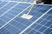 Close-up Of Professional Cleaning Of Solar Panels With A Mob. Concept Of Solar Power Plant Cleaning  poster